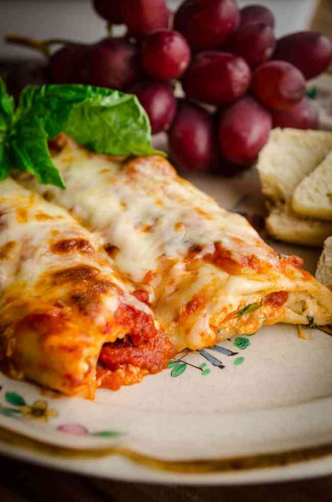 A close-up of Meatless Monday Cheese Stuffed Manicotti sits on a plate garnished with a sprig of fresh basil.