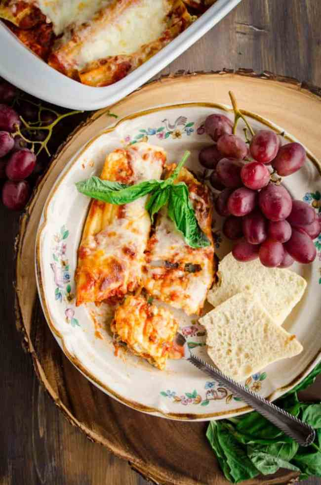 a serving of Meatless Monday Cheese Stuffed Manicotti sits on a plate surrounded by red grapes, sliced baguettes, and fresh basil.