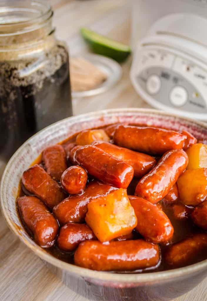 A bowl of Slow Cooker Hawaiian Little Smokies with chunks of pineapple in it sits in front of a slow cooker - The Goldilocks Kitchen