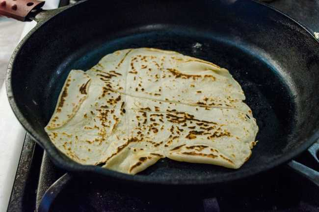 Spotty brown Norwegian Lefse cooks in a cast iron skillet - The Goldilocks Kitchen