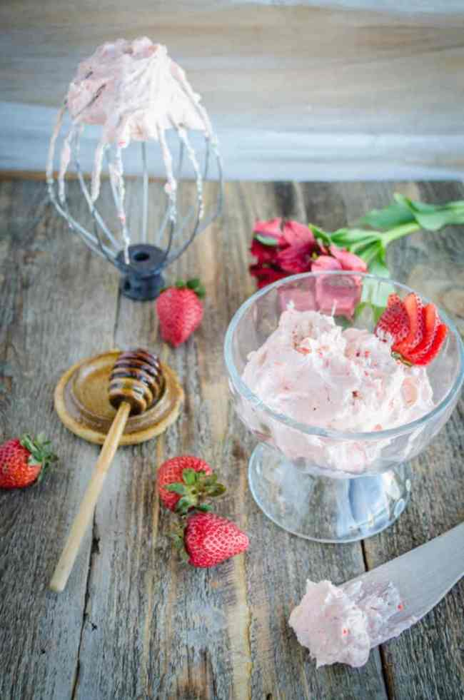 Whipped Strawberry Honey Butter sits in a glass bowl surrounded by fresh strawberries, a honey wand, and a stand mixer whip attachment which also has Whipped Strawberry Honey Butter on it. - The Goldilocks Kitchen