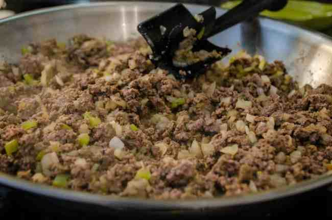 Hamburger, onion, green chile, cumin and chili powder cook in a skillet to make 30 Minute Chili Mac - The Goldilocks Kitchen