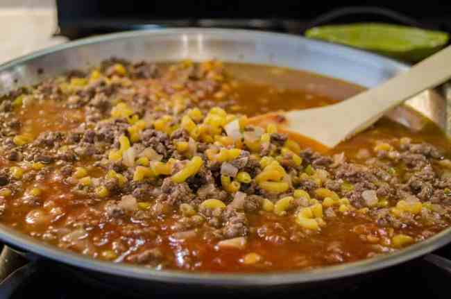 Elbow Macaroni, chicken broth and tomato sauce are stirred into seasoned ground beef to make 30 Minute Chili Mac - The Goldilocks Kitchen