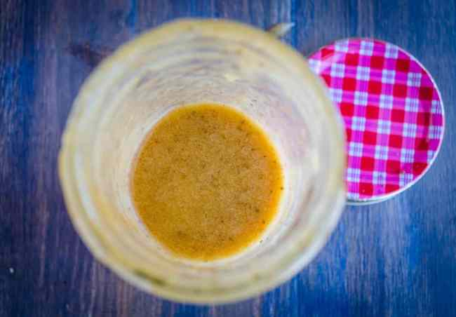 looking down into a glass mason jar filled with Ten Dollar Dressing. - The Goldilocks Kitchen