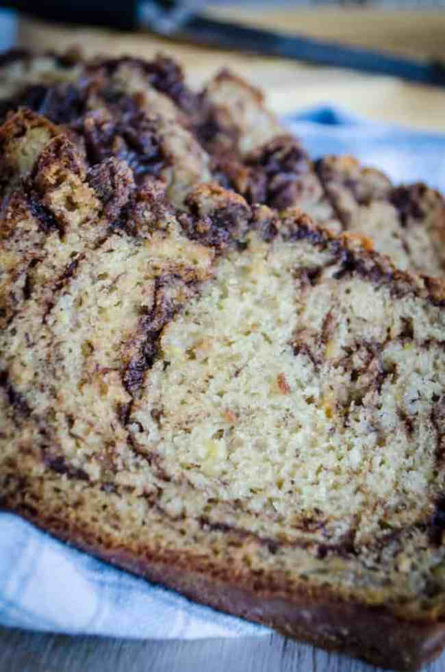 Slices of Nutella Banana Bread sit on a blue gingham tea towel. - The Goldilocks Kitchen