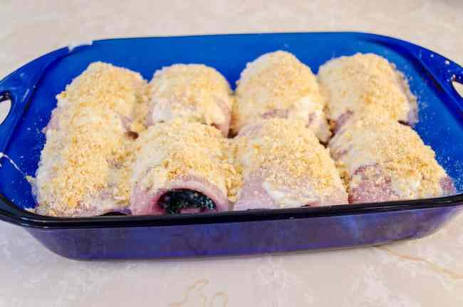 Stuffed fish bundles in a blue baking dish are topped with crushed Ritz crackers for a nice crunchy crust on Creamy Stuffed Fish Florentine - The Goldilocks Kitchen