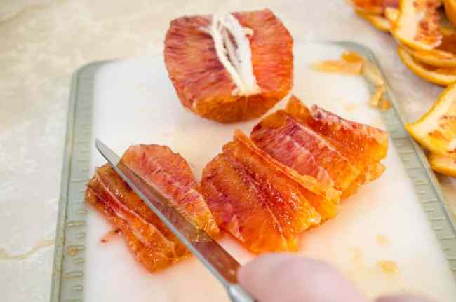 Blood orange is segmented into thin wedges with a knife on a cutting board for Feta Citrus Salad - The Goldilocks Kitchen