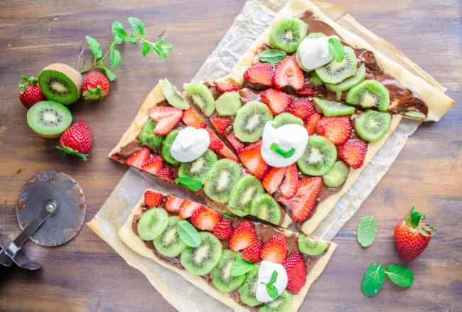 Looking down on a Nutella Pizza sliced into diagonal shapes, surrounded by whole kiwis and strawberries and sprigs of mint - The Goldilocks Kitchen