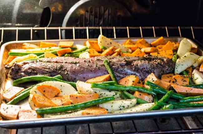 A seasoned pork tenderloin is surrounded by sliced apple, sweet potato and green beans all roasting in a sheet pan in the oven for Roasted Pork Apple Sweet Potato Dinner - The Goldilocks Kitchen