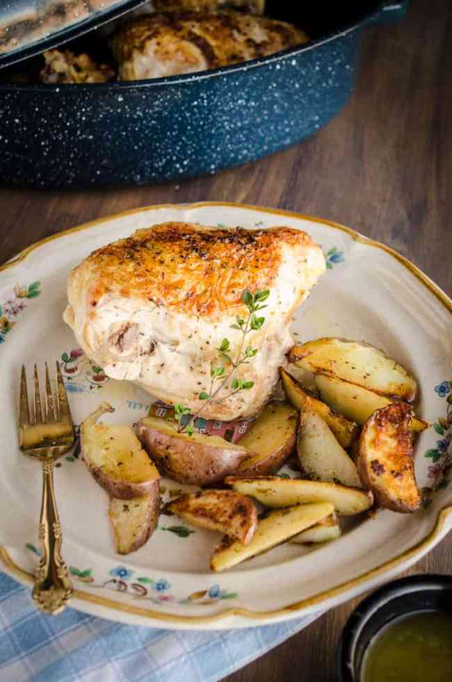 A roasted chicken breast sits on a decorative plate with browned and seasoned red potato wedges garnished with a sprig of thyme for Weeknight Roasted Chicken Breast with Red Potatoes recipe - The Goldilocks Kitchen