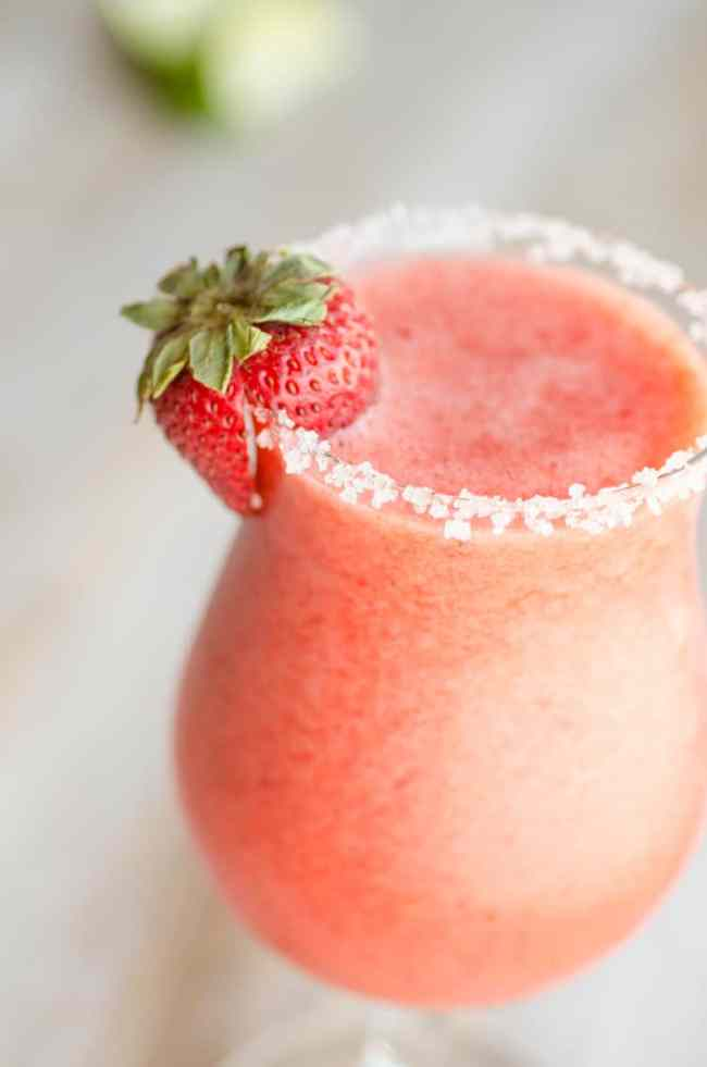 A close up of a fresh strawberry garnishing a glass of Fresh Virgin Strawberry Margaritas.