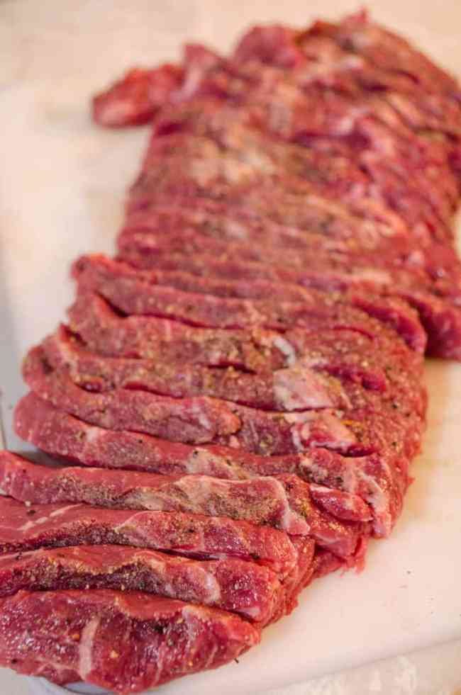 A beef steak seasoned and sliced into 1/2 inch slices for Slow Cooker Beef and Barley Stew.
