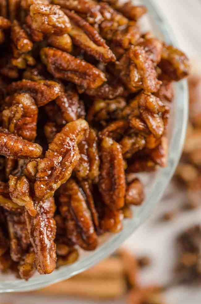 A close up picture of Candied Spice Pecans in a glass bowl - The Goldilocks Kitchen