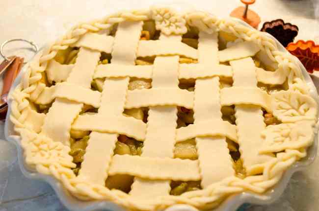 A lattice top is placed over Green Chile Apple Pie - The Goldilocks Kitchen