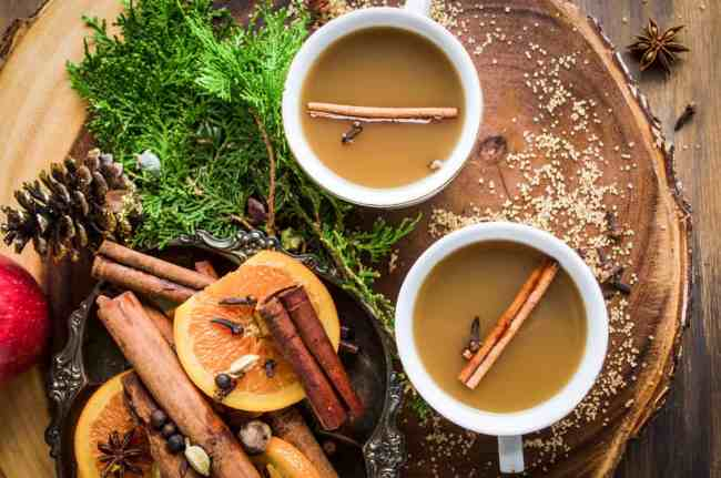 Mulled Apple Cider a.k.a. Wassail in two white mugs with a cinnamon stick and cloves floating on top.