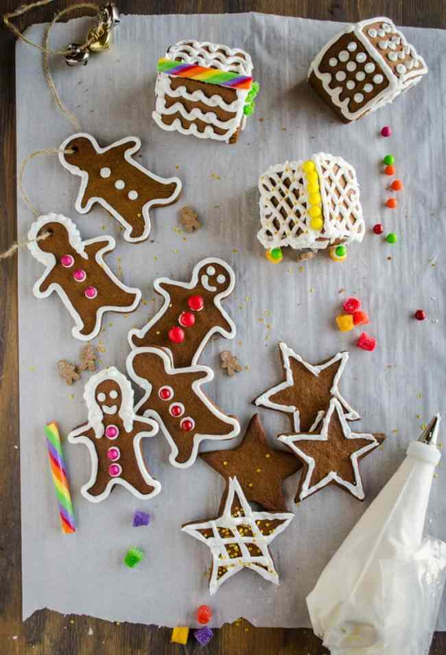 Easy Gingerbread Cookies shaped like gingerbread men, women, stars and mini-houses, are all decorated with white frosting and candy. - The Goldilocks Kitchen