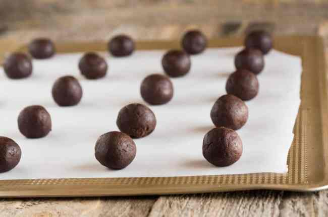 Chocolate dough balls sit in rows on a baking sheet lined with parchment paper for making Homemade Oreo Cookies - The Goldilocks Kitchen