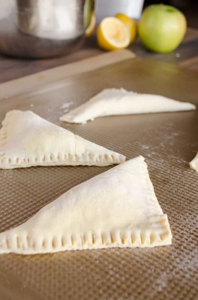 Folded Easy Apple Turnovers with crimped edges sit on a baking sheet waiting to be baked in the oven- The Goldilocks Kitchen