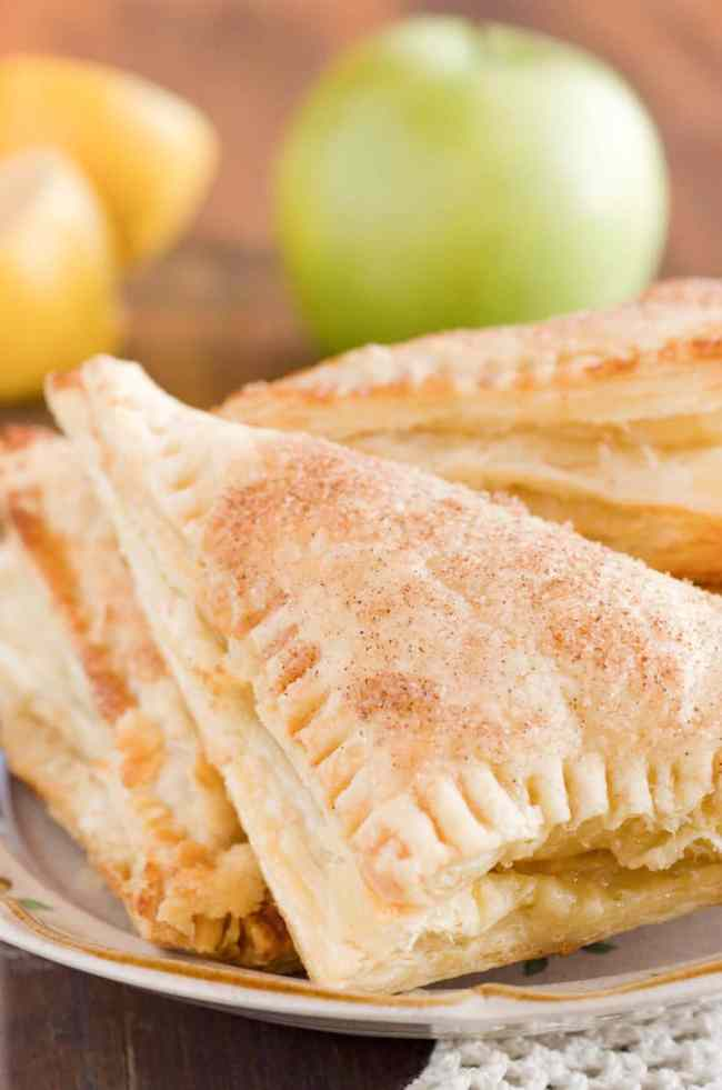 A close up picture of three Easy Apple Turnovers on a small plate with an apple and lemons in the background - The Goldilocks Kitchen