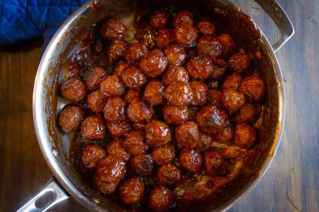Looking down on Cranberry Ginger Meatballs in a stainless steel pan covered in sauce - The Goldilocks Kitchen