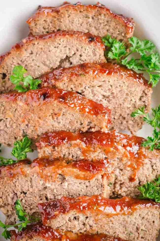 Glazed Meatloaf Slices sit in a white ceramic serving dish and are garnished with parsley - The Goldilocks Kitchen