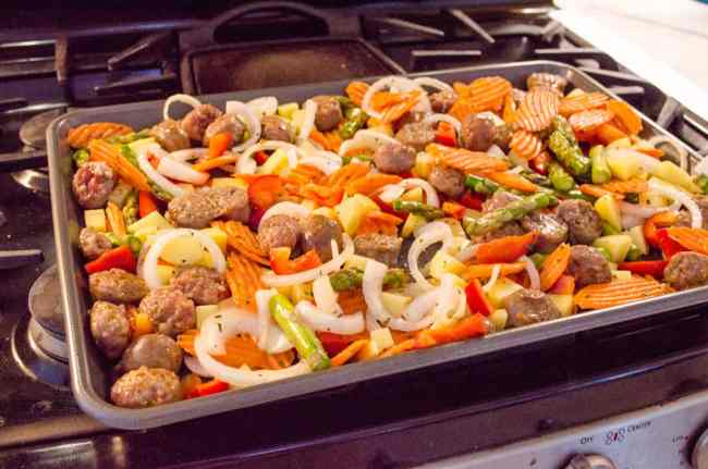 30 Minute Italian Sausage Sheet Pan Dinner sitting on the stovetop ready to be placed in the oven - The Goldilocks Kitchen