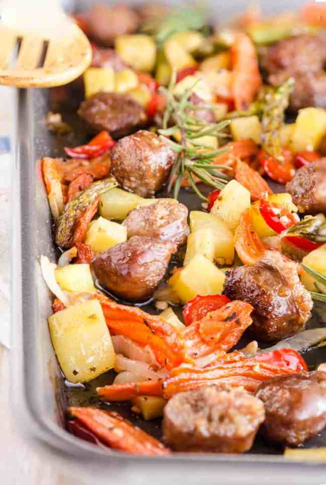 30 Minute Italian Sausage Sheet Pan Dinner close up pic in the sheet pan showing roasted carrots, potatoes, sausage pieces, red bell pepper and asparagus - The Goldilocks Kitchen