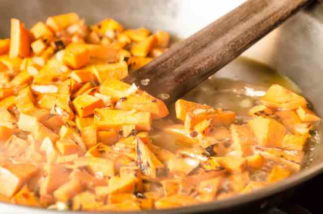 Diced sweet potato and onion is sauteed in a stainless steel skillet for Black Bean Sweet Potato Enchiladas - The Goldilocks Kitchen