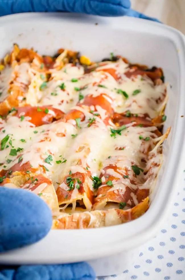 A white casserole dish full of Black Bean Sweet Potato Enchiladas - The Goldilocks Kitchen