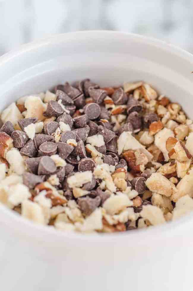Mini-chocolate chips, diced pecans, and diced freeze dried apple slices mixed together in a white ceramic cup as a topping for Applesauce Picnic Cake - The Goldilocks Kitchen