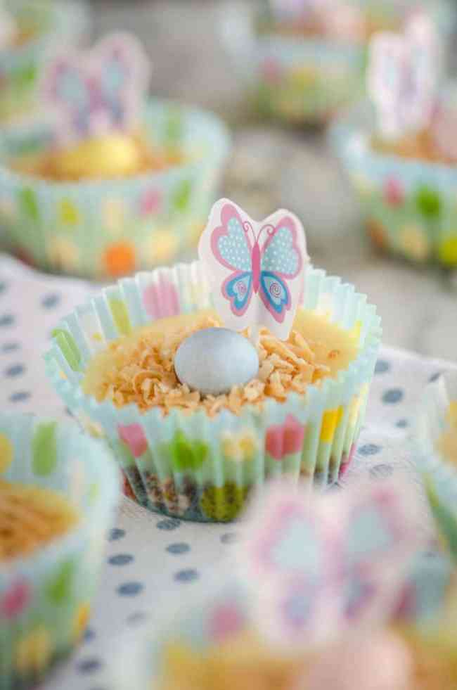 A cupcake is decorated with toasted coconut a little blue candy egg and a paper butterfly for Strawberry Mini-Cheesecakes - The Goldilocks Kitchen