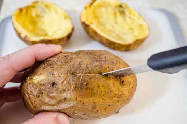 Holding a baked potato sideways to slice it in half for Make Ahead Twice Baked Potatoes - The Goldilocks Kitchen