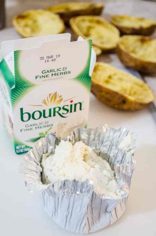 A chunk of boursin cheese sits in it's foil wrapper in front of the packaging box with potato shells in the background for making Make Ahead Twice Baked Potatoes - The Goldilocks Kitchen