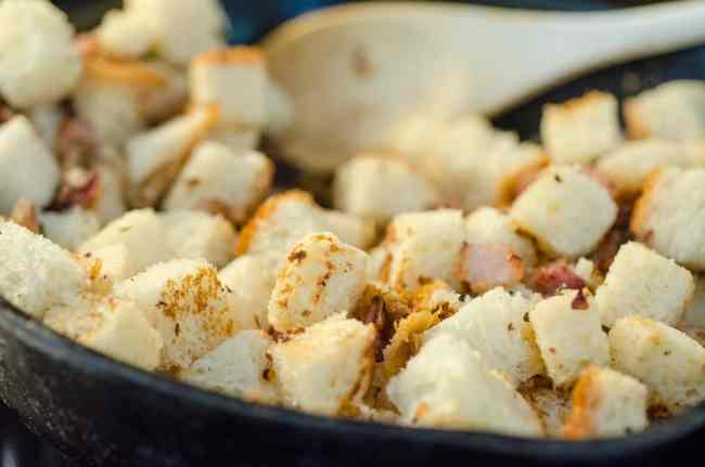 Cubes of hearty bread toast in a cast-iron skillet to make a Bacon Cheddar 30 Minute Skillet Strata - The Goldilocks Kitchen