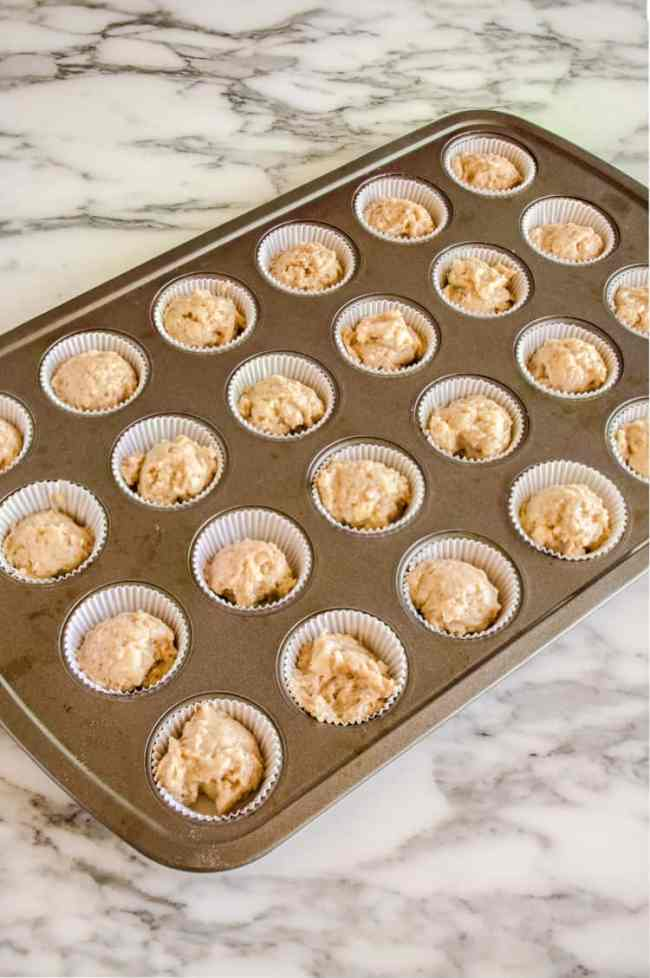 Mini muffin tin with white cupcake liners is filled with Apple Cinnamon Cupcakes dough. - The Goldilocks Kitchen