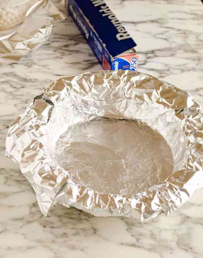 A pie plate is completely covered with aluminum foil that has been pressed down right over the bottom pie crust to show how to prebake a pie crust - The Goldilocks Kitchen