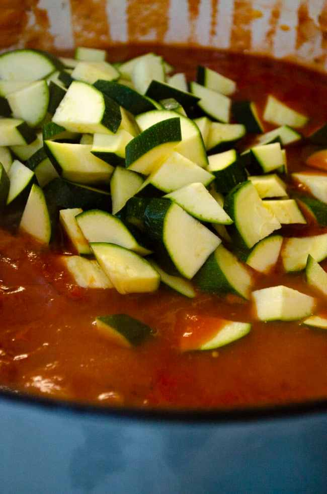 Chopped fresh zucchini is added into a Dutch oven cooking green chile squash goulash.