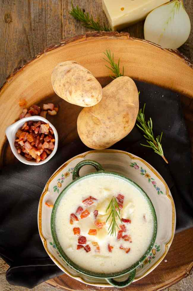 Looking down on a wooden table with a bowl of Gluten-free Swiss Potato Soup next to some russet potatoes, a tiny bowl of chopped bacon, and other ingredients.