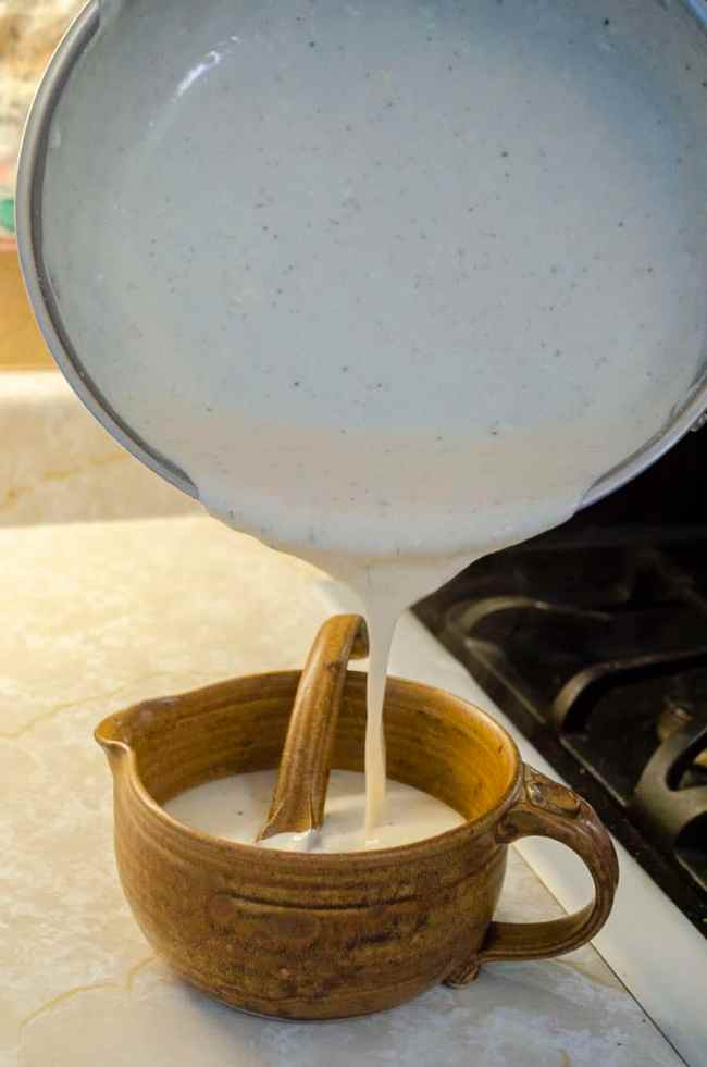 Homemade White Country Gravy is poured from a saute pan into a brown ceramic gravy boat with a ladle.