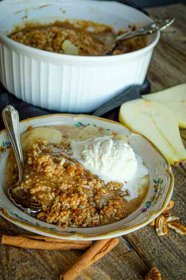 A closeup of a serving of Ginger-Pear Crisp showing the crumbly brown topping and thinly sliced cooked pears below.