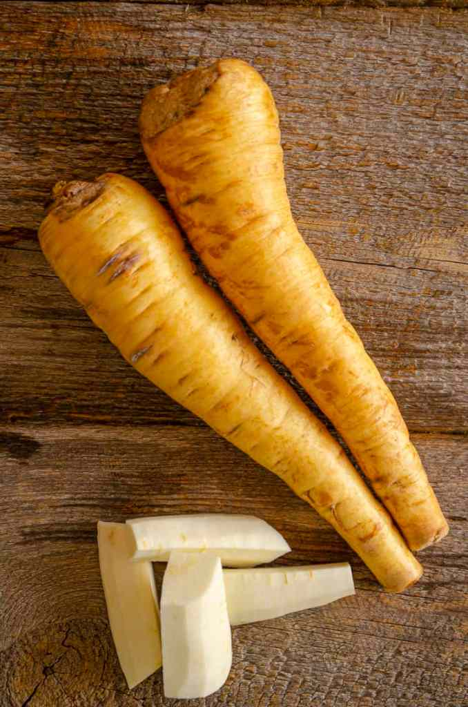 Two golden parsnips sit on a barn wood table next to some peeled and chopped pieces of fresh parsnip.