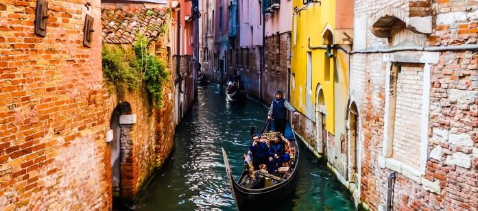 People enjoying gondola ride in Venice