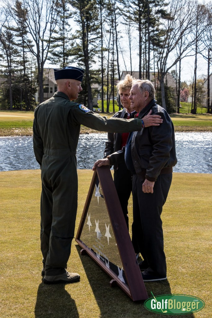 Lt. Colonel Rooney presents Jack and Barbara Nicklaus with a folded flag at American Dunes