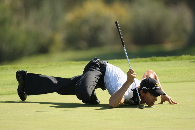 Camilo Villegas turns into Spiderman to read the lines on a green