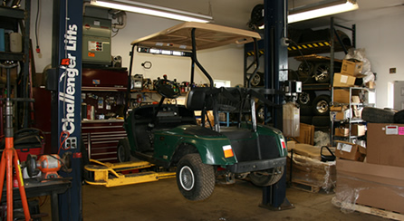 green golf cart on lift for repair
