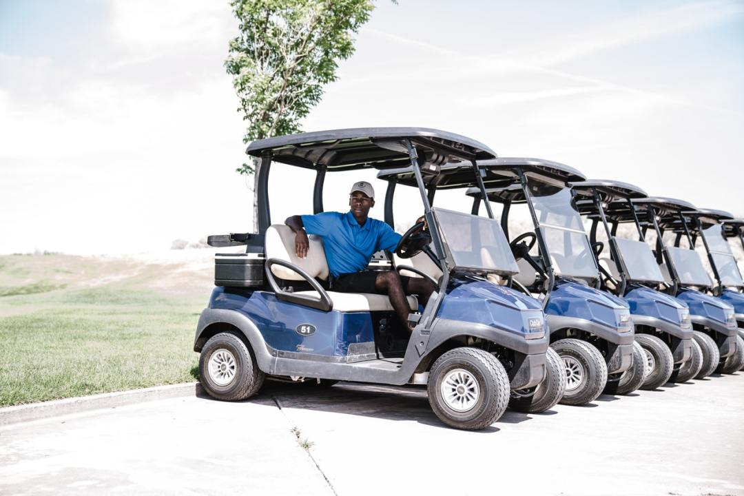 Man in blue shirt riding a golf cart with lift kits