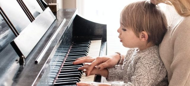 A woman and a child playing the piano