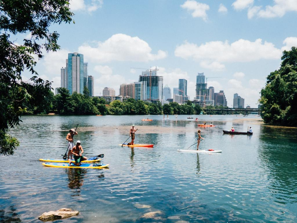 boats and paddle boards on river in front of austin skyline