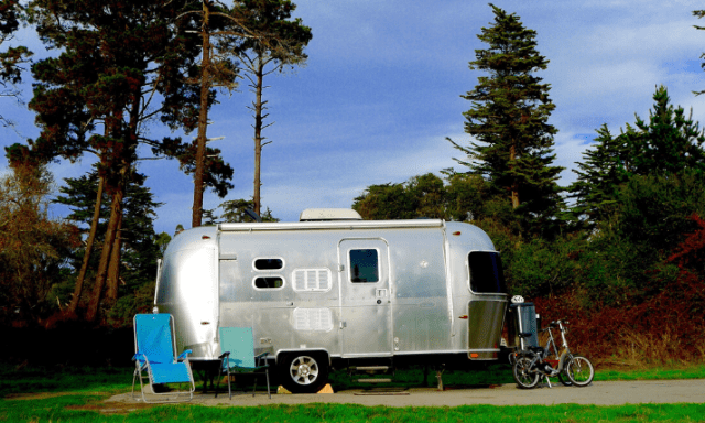 airstream trailer in campsite near trees