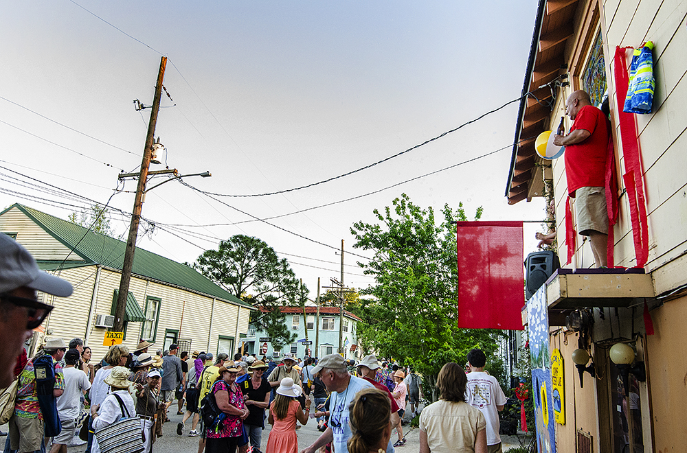April 22, 2016 - New Orleans, LA: A man stands above the crowd, overlooking the street party beginning to form at The Bubble House, the first residence festival goers pass when exiting the New Orleans Jazz and Heritage Festival onto Mystery Street. The Bubble House is exactly what it sounds like, a house full of partiers that emits a constant stream of bubbles, each year with a different theme. This year's theme is Summer Camp. (Photo by Katie Sikora)